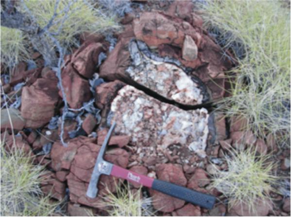 Cette photo représente un assemblage de laves en coussin, contenant un amas de quartz et de carbonate ayant rempli des cavités de dégazage. Le fait que ces cavités ne sont pas déformées indiquent que le remplissage s'est fait peu après la mise en place des laves. Les inclusions fluides étudiées proviennent de fractions de quartz séparées de ce remplissage. Ces laves se situent au sommet de la formation Dresser, datée à 3,5 milliards d'années, dans la région de North Pole (Pilbara, Australie du sud-ouest; photo B. Marty).