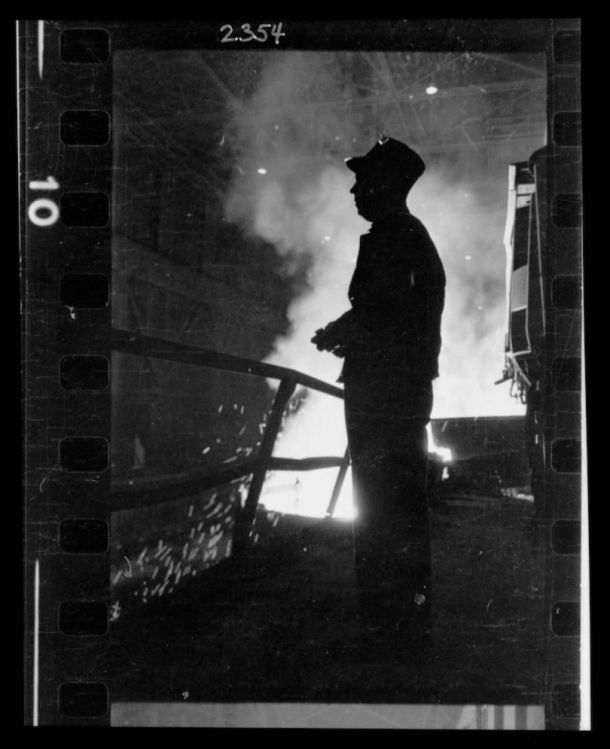 Steel worker standing in mill with smelter in the background, in Chicago, Illinois